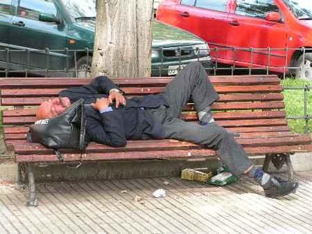 Indigente durmiendo en un banco del parque