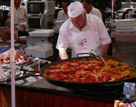 cocinero atendiendo una gran paella