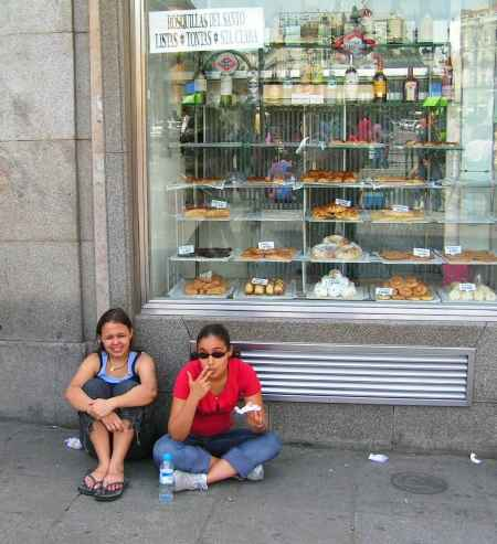 dos chicas sentadas en la calle