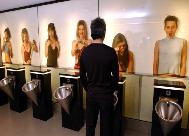 urinario de hombres con posters de mujeres