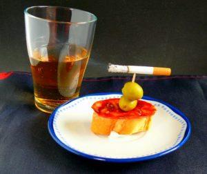 VAso de cerveza, cigarrillo y tapa